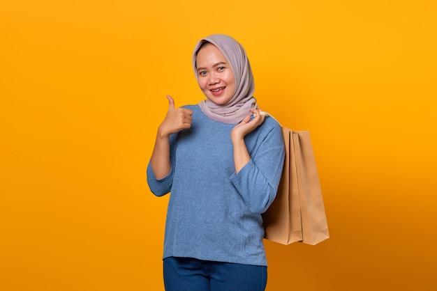 Porträt einer lächelnden asiatischen frau mit einkaufstasche und daumen nach oben über gelbem hintergrund