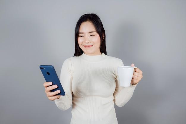Porträt einer lächelnden asiatischen frau trägt ein smartphone auf grauem hintergrund
