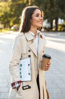 Porträt einer lächelnden attraktiven frau mit mantel, die kaffee zum mitnehmen trinkt und die zwischenablage beim gehen auf der stadtstraße hält