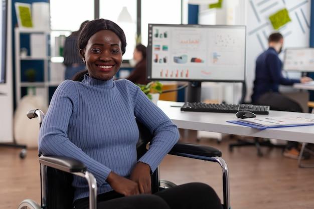 Porträt einer lächelnden behinderten gelähmten afroamerikanischen geschäftsfrau im rollstuhl
