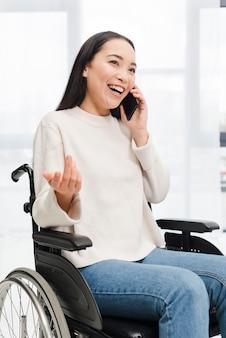 Porträt einer lächelnden behinderten jungen frau, die auf dem rollstuhl sitzt, zuckend mit dem handy