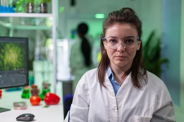 Porträt einer lächelnden biologenfrau, die genetisch veränderte organismen analysiert analyzing