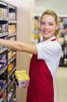 Porträt einer lächelnden blonden arbeitskraft, die ein produkt im regal nimmt