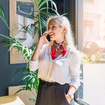 Porträt einer lächelnden blonden jungen frau, die am handy spricht