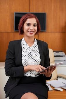 Porträt einer lächelnden, eleganten geschäftsfrau, die auf dem schreibtisch sitzt und die anwendung zum organisieren und planen verwendet