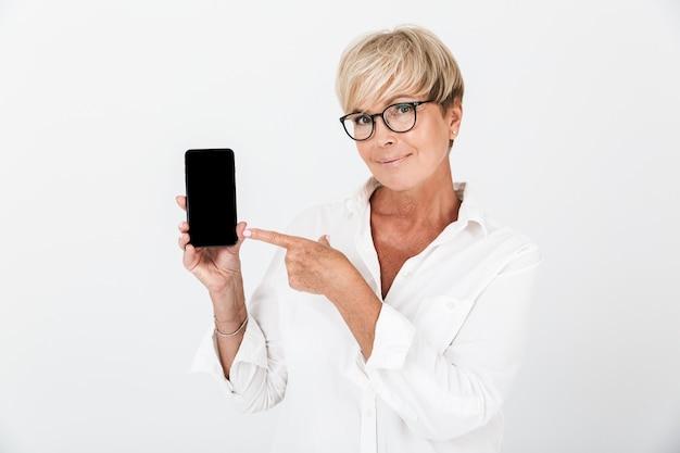 Porträt einer lächelnden erwachsenen frau mit kurzen blonden haaren, die ein handy hält und einen schwarzen bildschirm zeigt, der über einer weißen wand im studio isoliert ist?