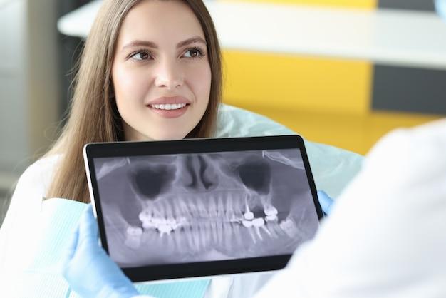 Porträt einer lächelnden frau beim zahnarzttermin, die tablette mit einem röntgenbild des kiefers hält