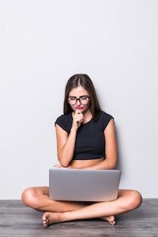 Porträt einer lächelnden frau, die auf dem boden sitzt und laptop lokalisiert auf grauem hintergrund