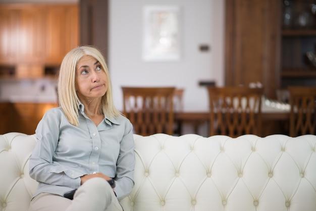 Porträt einer lächelnden frau, die auf der couch in ihrem haus sich entspannt