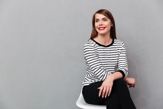 Porträt einer lächelnden frau, die auf stuhl sitzt