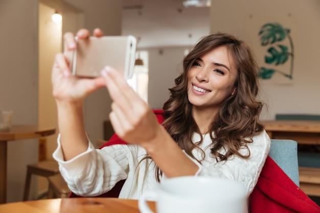 Porträt einer lächelnden frau, die ein selfie nimmt