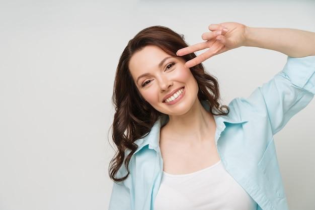 Porträt einer lächelnden frau, die ein victory-zeichen zeigt und in eine kamera schaut, die auf einem weißen isoliert ist
