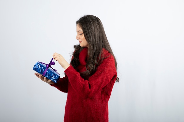 Porträt einer lächelnden frau, die eine weihnachtsgeschenkbox mit lila band öffnet.