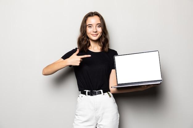 Porträt einer lächelnden frau, die finger auf leerem laptop-computerbildschirm über grau zeigt