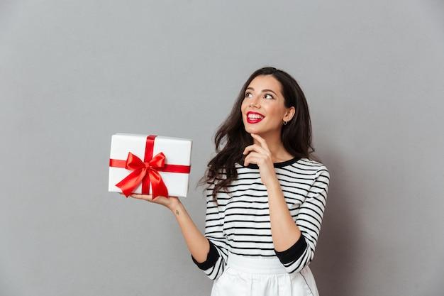 Porträt einer lächelnden frau, die geschenkbox hält