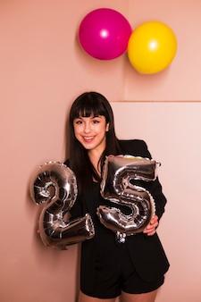 Porträt einer lächelnden frau, die in der hand 25 silbernen feierballon hält