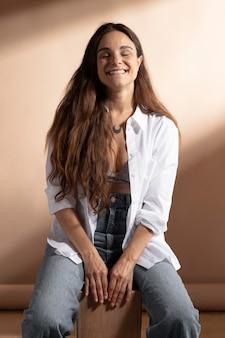 Porträt einer lächelnden frau, die in einem weißen hemd posiert