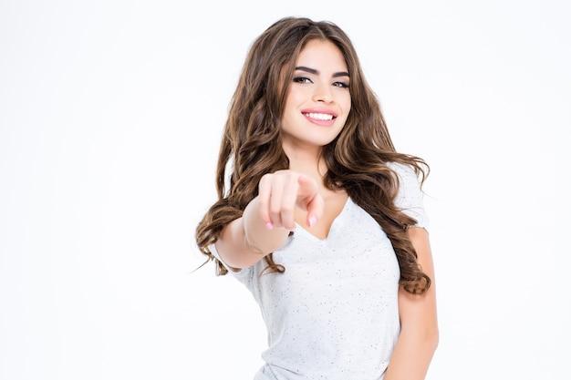 Porträt einer lächelnden frau, die mit dem finger auf eine weiße wand zeigt