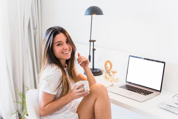 Porträt einer lächelnden frau, die nahe dem schreibtisch mit laptop sitzt