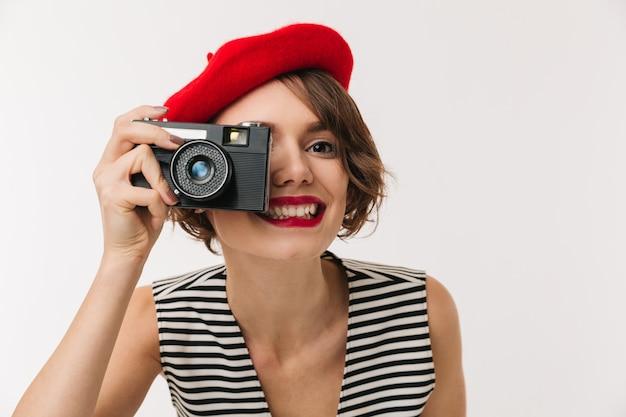 Porträt einer lächelnden frau, die rote baskenmütze trägt