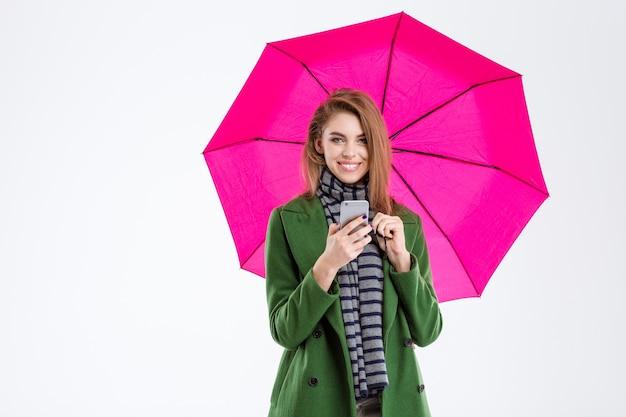 Porträt einer lächelnden frau, die smartphone unter regenschirm hält und kamera auf weißem hintergrund betrachtet