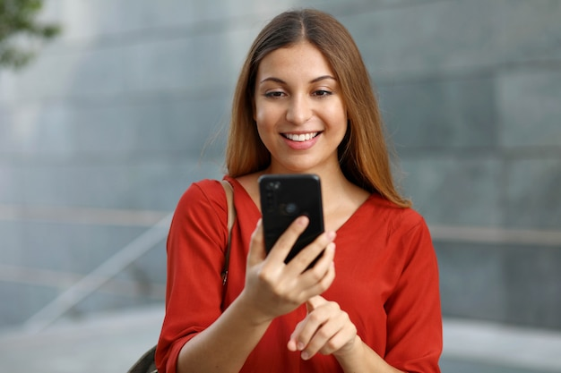 Porträt einer lächelnden frau, die textnachricht von ihrem telefon sendet