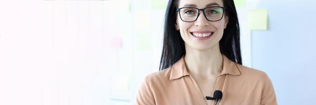 Porträt einer lächelnden frau mit brille mit mikrofon auf bluse