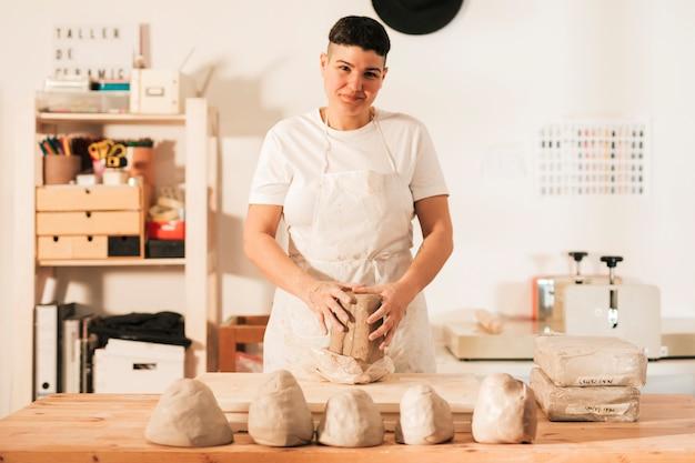 Porträt einer lächelnden frau mit geknetetem lehm in der werkstatt