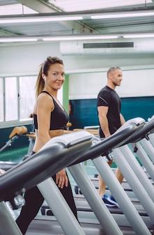 Porträt einer lächelnden frau mit kopfhörern, die über ein laufband im fitnesscenter trainiert