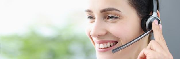 Porträt einer lächelnden frau mit kopfhörern und mikrofon-kundendienstmitarbeiter