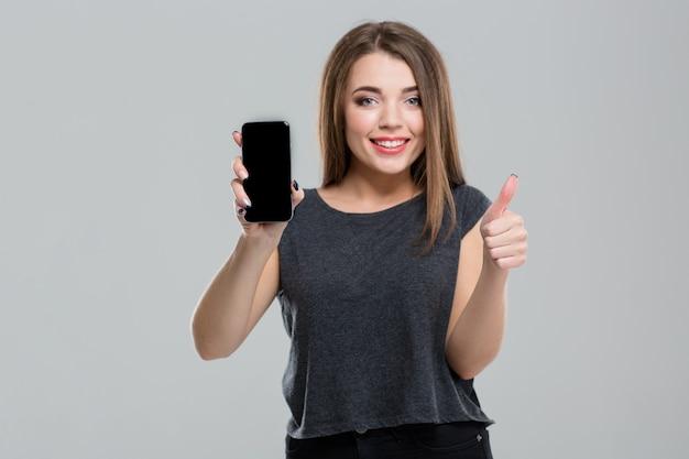 Porträt einer lächelnden frau mit leerem smartphone-bildschirm und daumen nach oben isoliert auf weißem hintergrund