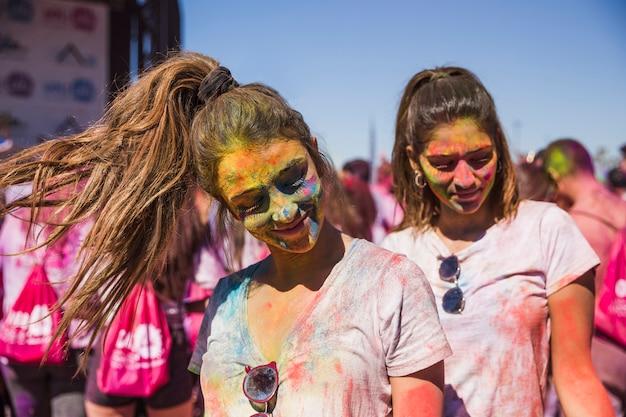 Porträt einer lächelnden freundin zwei bedeckte ihr gesicht mit holi farbe