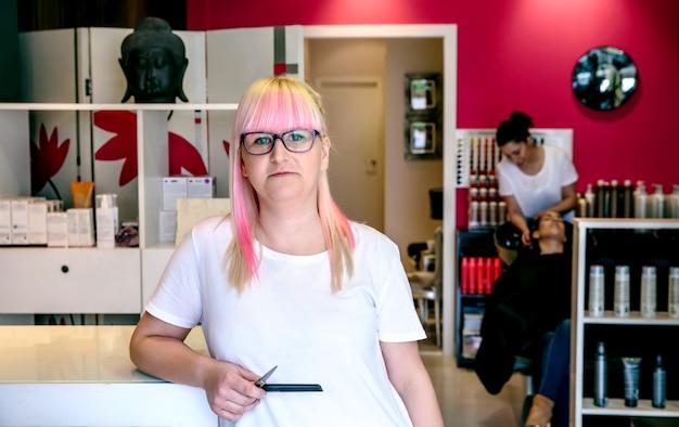 Porträt einer lächelnden friseurin, die in einem haar- und schönheitssalon steht, mit einem mitarbeiter, der im hintergrund die haare der frau wäscht
