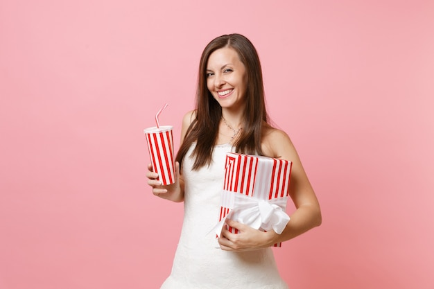 Porträt einer lächelnden, fröhlichen frau im weißen kleid, die eine rote schachtel mit geschenkgeschenk und eine plastiktasse mit cola oder soda hält