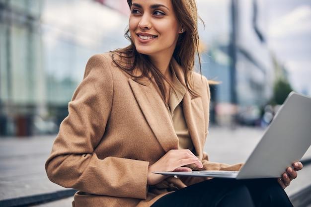 Porträt einer lächelnden, fröhlichen hübschen frau mit einem laptop auf den knien, die wegschaut