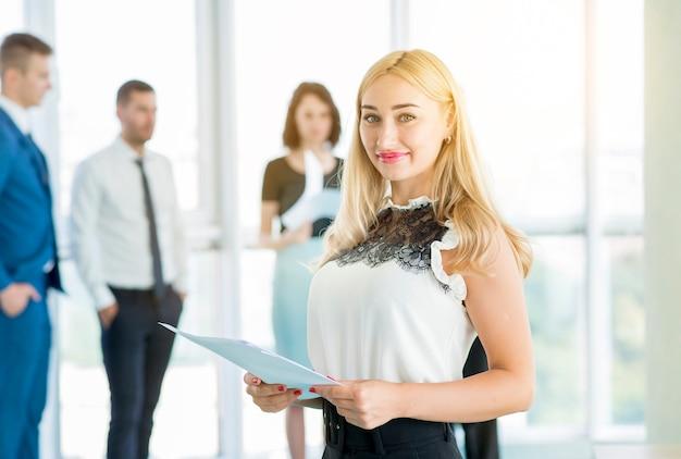 Porträt einer lächelnden geschäftsfrau, die dokument im büro hält