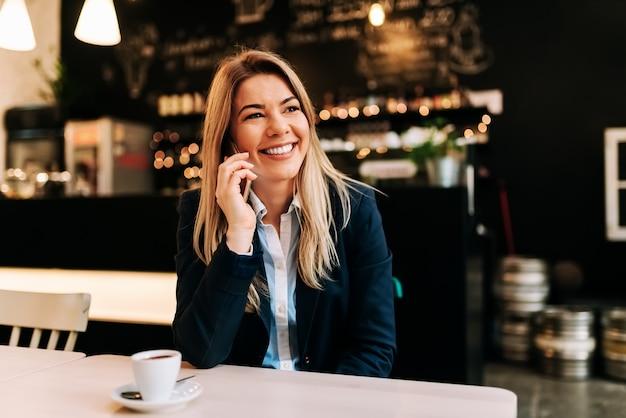 Porträt einer lächelnden geschäftsfrau, die im restaurant an einem telefon spricht.