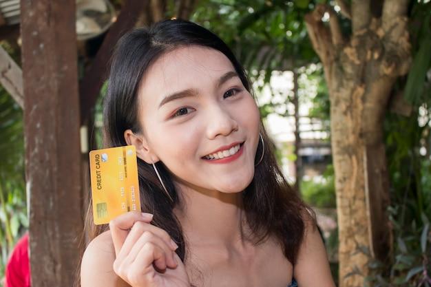 Porträt einer lächelnden glücklichen asiatischen frau, die kreditkarte hält