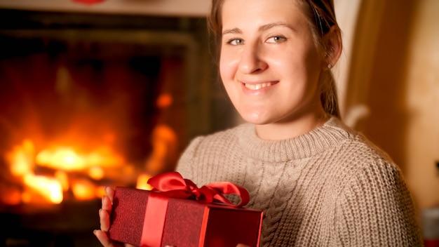 Porträt einer lächelnden, glücklichen frau, die am kamin sitzt und eine rote geschenkbox hält