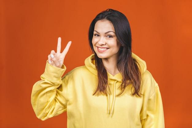 Porträt einer lächelnden glücklichen frau, die siegeszeichen zeigt und kamera lokalisiert auf dem orangefarbenen hintergrund zeigt.