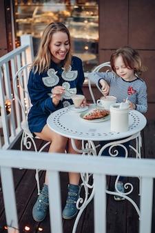 Porträt einer lächelnden glücklichen frau mit blonden haaren im blauen kleid mit enten und blauen stiefeln, die mit ihrer tochter im café eine tasse kaffee genießt. reizendes mädchen, das kakao rührt, das draußen von der mutter am tisch sitzt.