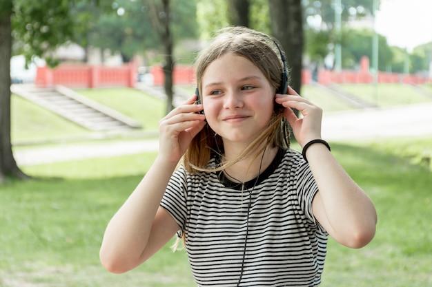 Porträt einer lächelnden hörenden musik des jungen mädchens am park