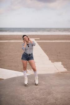 Porträt einer lächelnden hörenden musik des jungen weiblichen schlittschuhläufers auf kopfhörer am strand