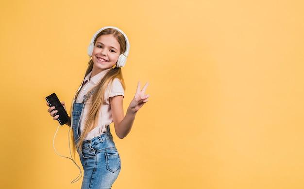 Porträt einer lächelnden hörenden musik des mädchens auf dem weißen kopfhörer, der gegen gelben hintergrund gestikuliert