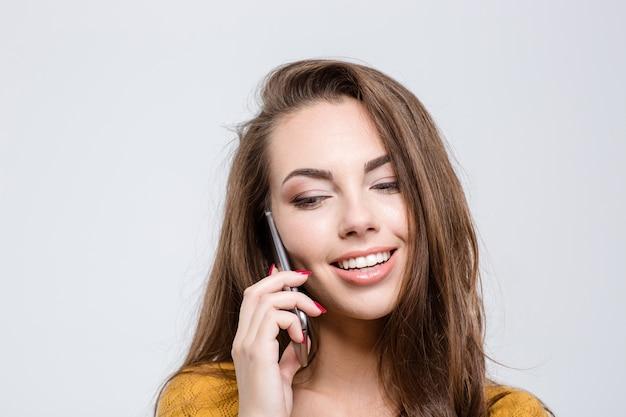 Porträt einer lächelnden hübschen frau, die am telefon spricht und auf einem weißen hintergrund isoliert