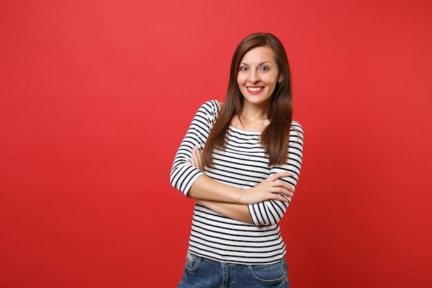 Porträt einer lächelnden hübschen jungen frau in lässiger gestreifter kleidung, die stehend die hände gefaltet hält