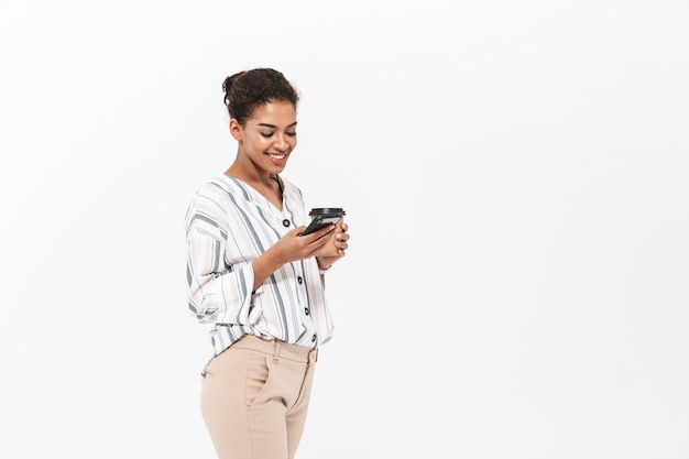 Porträt einer lächelnden jungen afrikanischen geschäftsfrau, die isoliert über weißer wand steht, kaffee zum mitnehmen trinkt und handy benutzt