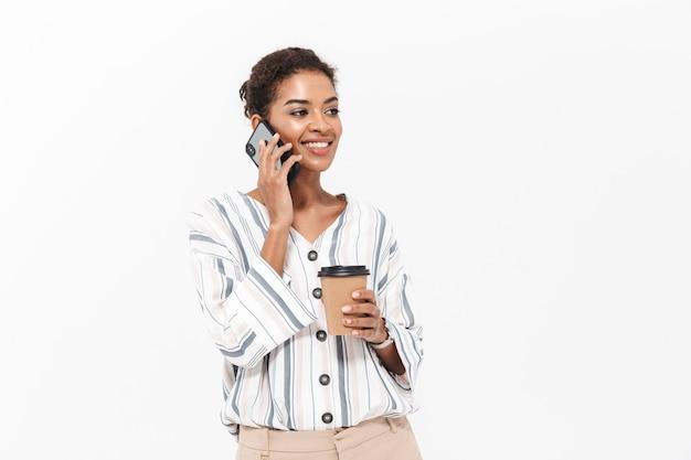 Porträt einer lächelnden jungen afrikanischen geschäftsfrau, die isoliert über weißer wand steht, kaffee zum mitnehmen trinkt und mit dem handy spricht