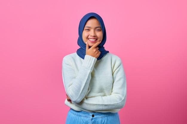 Porträt einer lächelnden jungen asiatin, die das kinn mit der hand auf rosafarbenem hintergrund berührt
