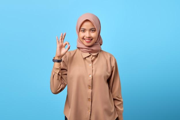Porträt einer lächelnden jungen asiatin, die mit den fingern ein okayzeichen macht, übergibt blauem hintergrund